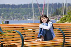 Young girl enjoying sun on bench by lake Royalty Free Stock Photos