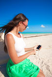 Young girl enjoys her phone on an exotic beach Royalty Free Stock Images