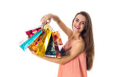 Young girl enjoys and holds in his hand a beautiful colored bags isolated on white background Royalty Free Stock Images