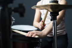 5 year old girl practices the drums. A young girl enjoys practicing the drums whilst wearing adequate ear protection stock images