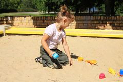 Young girl enjoys in the sandbox. Children's Playground. Sandbox. The girl begins to build with sand. Season summer Royalty Free Stock Images