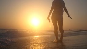 A young girl enjoys the sunset and the sea, jumping on the water with happiness. HD, 1920x1080. slow motion. stock video footage