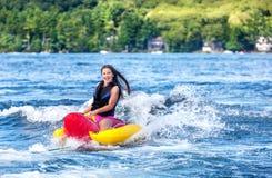 Young girl enjoys tubing on lake Royalty Free Stock Photography