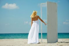 Young girl entering door on sea background Royalty Free Stock Photos
