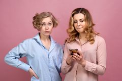 A young girl with envy and discontent turns away from her friend because she with happy expression writes a message on smartphone stock photography