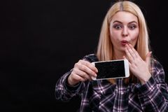 A girl is holding a broken smartphone and looking at it frustratedly. On a black background. Close-up. stock images