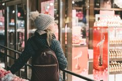 A young girl in the evening is looking at the brightly shining showcase of a candy store with interest royalty free stock photography