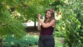 A young girl with excess weight walks in a park among green trees. Plus size model stock video footage