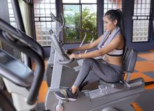 Young girl exercise bike cardio workout at fitness gym. Of woman taking weight loss with machine aerobic for slim and firm Athlete builder muscles lifestyle stock photography