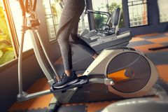Young girl exercise bike cardio workout at fitness gym of woman Royalty Free Stock Photos