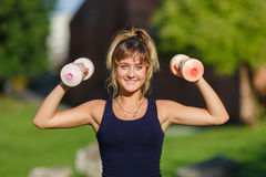 Young girl exercising with dumbbell Stock Photo