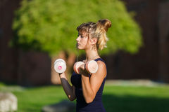 Young girl exercising with dumbbell Royalty Free Stock Images