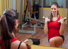 Young girl exercising with dumbbells at home Stock Photo