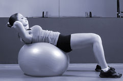 Young girl exercising on the fitness ball in modern gym royalty free stock image