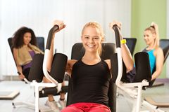 Young girl exercising at gym smiling Stock Image