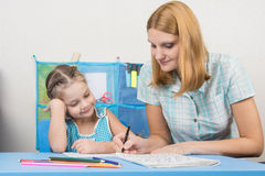 A young girl explains the five-year girl how to write letters Stock Image