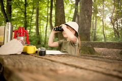 Young girl explores  nature with binoculars on camping trip Stock Photos