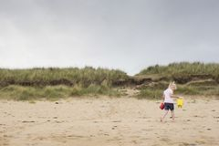 A young girl explores a Scottish beach with bucket and spade. . stock photography