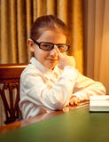 Young girl in eyeglasses sitting behind desk Stock Photos
