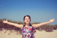Young girl with eyes shut enjoying sun and wind. On the sea coast Stock Photos