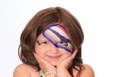 Young Girl with Face Paint.  Smiling with hands under chin. Royalty Free Stock Photography