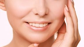 Young girl facelift lotion. Plastic face tooth. Massage therapy. Beauty woman skin cream stock photo