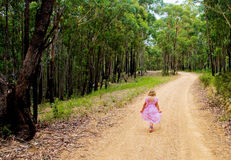 Young girl faces long walk home. Young girl in pink dress faces long walk on country road on her own Stock Photography