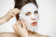 Young girl with facial mask looking at camera over white background. Cosmetic procedure. Beauty spa and cosmetology. Copy space Stock Photos