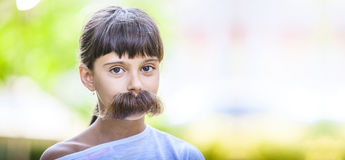 Young girl with fake mustaches hiding her smile. Stock Photos