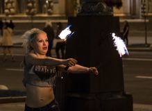 A young girl fakir in the center of the city arranges a fiery show. royalty free stock image