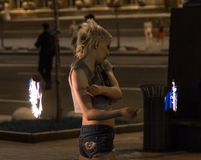 A young girl fakir in the center of the city arranges a fiery show. stock photo
