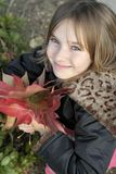 Young girl in the Fall. Young girl with blue eyes holding fall leaves, vertical stock images