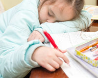 Young girl falling asleep doing homework Royalty Free Stock Images