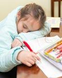 Young girl falling asleep doing homework Stock Images