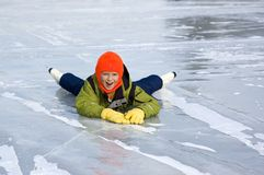 Young Girl Falls Learning to Skate. Cute young girl dressed colorfully falls while learning to ice skate Royalty Free Stock Images