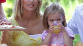 Young Girl At Family Meal Drinking Orange Juice stock footage