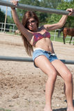 Young girl in the farm farm with top bikini and shorts. Young girl in the farm, wear sunglasses , short jean and bra posing outside of the horse fenced area Stock Photography