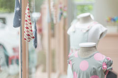 Young girl fashion dress in childrenswear fashion shop window Stock Images
