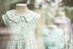 Young girl fashion dress in childrenswear fashion shop window Royalty Free Stock Images