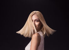Young girl fashion model face head blond hair moving. Young adult girl woman, 19 fashion model spinning turning moving head face blond hair. Black background Stock Image
