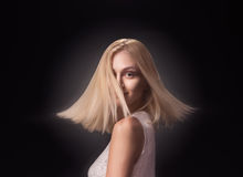 Young girl fashion model face head blond hair moving. Young adult girl woman, 19 fashion model spinning turning moving head face blond hair. Black background Stock Photo