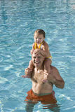 Young girl on father shoulders in swimming pool Royalty Free Stock Image