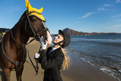 Young girl with a favorite horse on the beach. Royalty Free Stock Image