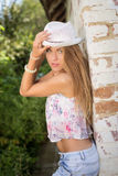 Young girl in fedora hat leaning at old brick Stock Photography