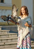 Young girl feed dove. Young girl with curly hair feed dove Stock Photography