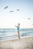 Young Girl are Feeding Seagulls. Young Girl at Beach are Feeding Seagulls Stock Images