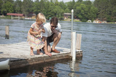 Young girl feeds fish from a dock in Minnesota with her father Stock Photo