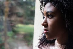 Black girl watching out of the window. Young girl feeling alone and solitude at home royalty free stock photo