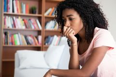 Young girl feeling alone and solitude at home. Sad woman lying on the couch at home feeling bad stock photography