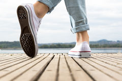 Young girl feet with shoes on a wood pier Royalty Free Stock Image